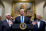President Donald Trump, accompanied by Agriculture Secretary Sonny Perdue, left, speaks during a meeting to support America's farmers and ranchers in the Roosevelt Room of the White House, Thursday, May 23, 2019, in Washington. (AP Photo/Andrew Harnik)
