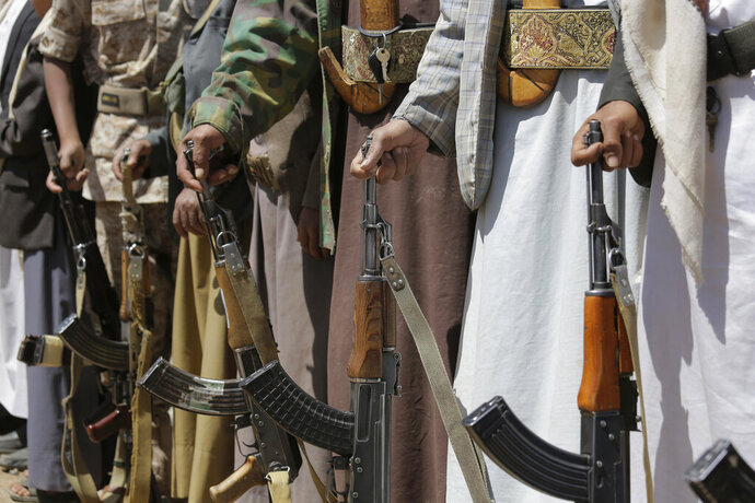 FILE - In this file photo dated Saturday Sept. 21, 2019, Shiite Houthi tribesmen hold their weapons during a tribal gathering showing support for the Houthi movement, in Sanaa, Yemen.  Iran-backed Houthi rebels and a Saudi-led coalition have fought Yemen's civil war to a stalemate, but officials in Sudan said on Saturday Nov. 16, 2019, an attack by Yemeni rebels killed six members of a Sudanese paramilitary force that's been fighting in Yemen.  (AP Photo/Hani Mohammed, FILE)