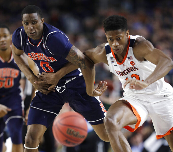 Auburn forward Horace Spencer, left, fights for a loose ball with Virginia guard De'Andre Hunter during the first half in the semifinals of the Final Four NCAA college basketball tournament, Saturday, April 6, 2019, in Minneapolis. (AP Photo/David J. Phillip)
