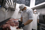 In this June 12, 2020 photo, a butcher cuts meat at Don Julio butcher's shop in Buenos Aires, Argentina. Don Julio's steakhouse turned itself into a high-end delivery butcher shop after the restaurant was forced to closed on March 20th due to the COVID-19 pandemic. (AP Photo/Victor R. Caivano)