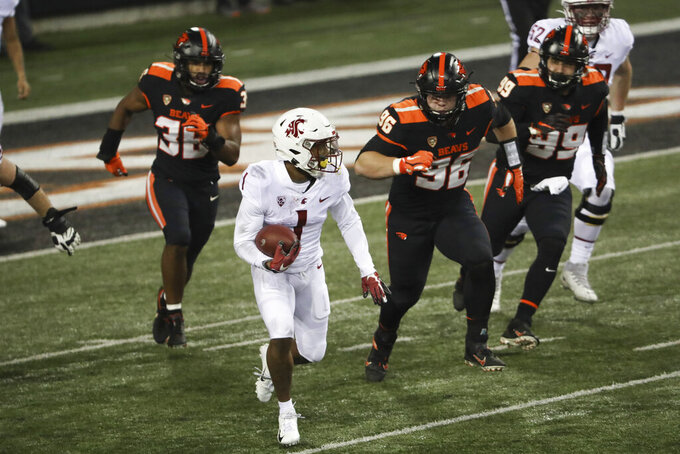 Washington State wide receiver Travell Harris (1) runs from Oregon State's Omar Speights (36), Simon Sandberg (96) and Isaac Hodgins (99) during the first half of an NCAA college football game in Corvallis, Ore., Saturday, Nov. 7, 2020. (AP Photo/Amanda Loman)