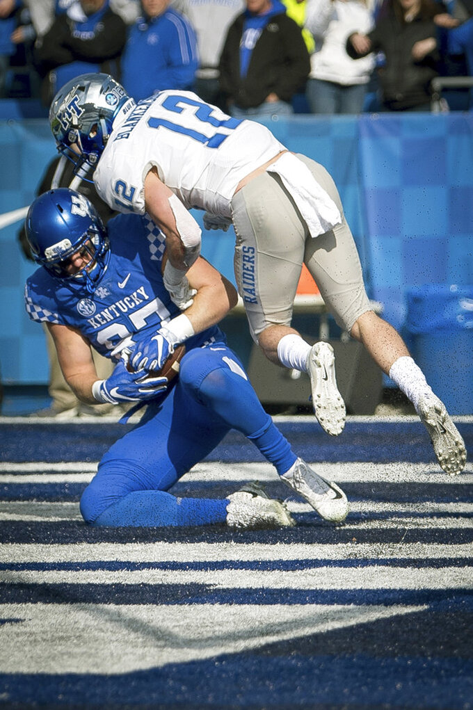 Kentucky tight end C.J. Conrad (87) scores a touchdown as he is tackled by Middle Tennessee safety Reed Blankenship (12) during the first half of an NCAA college football game in Lexington, Ky., Saturday, Nov. 17, 2018. (AP Photo/Bryan Woolston)