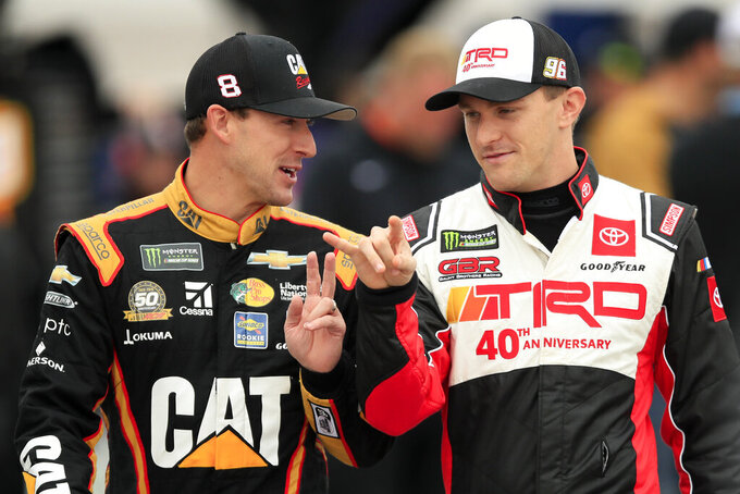Daniel Hemric, left, and Parker Kligerman, right, talk before qualifying for a NASCAR Cup Series auto race at Kansas Speedway in Kansas City, Kan., Saturday, Oct. 19, 2019. Hemric won the pole position for the race. (AP Photo/Orlin Wagner)