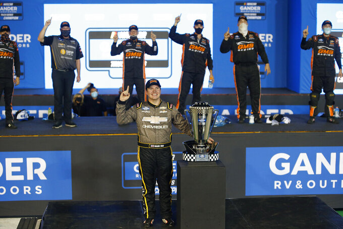 Sheldon Creed, center, stands with the season championship trophy in victory lane after winning the NASCAR Truck Series auto race at Phoenix Raceway, Friday, Nov. 6, 2020, in Avondale, Ariz. (AP Photo/Ralph Freso)