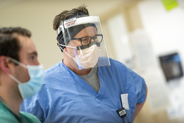 In this image provided Dartmouth-Hitchcock Health, Respiratory Care Practitioner Craig Skirvin, wears a face shield, Friday, May 1, 2020, at Dartmouth-Hitchcock Medical Center;s Medical Intensive Care Unit, where it cares for COVID-19 patients in Lebanon, N.H. The hospital had extra face shields but needed hand sanitizer, so it swapped with another hospital on one of several new online matchmaking platforms that enable hospitals  to swap supplies or get donations of them to quickly fill supply gaps. (Mark L. Washburn/Dartmouth-Hitchcock Health via AP)