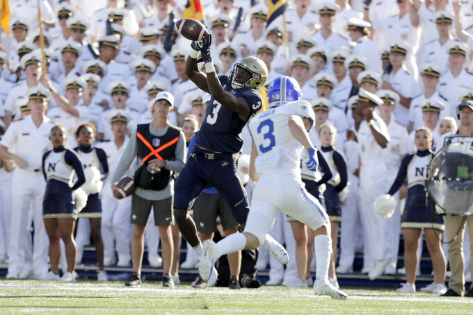 Navy wide receiver Mychal Cooper, left, makes a catch as Air Force defensive back Milton Bugg III moves in for the hit during the first half of an NCAA college football game Saturday, Oct. 5, 2019, in Annapolis, Md. (AP Photo/Julio Cortez)
