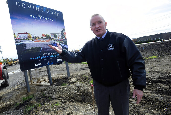 FILE - In this May 2019 file photo, Elk Grove Village Mayor Craig Johnson walks the $1 billion Elk Grove Technology Park which was the former 85-acre Busse Farm.Johnson came up with the idea of bowl sponsorship while he was in Wisconsin a couple winters ago. Elk Grove Village had been advertising on Chicago Cubs broadcasts, but it stepped back because of pricing and was looking for something new.  Johnson was watching a bowl game on TV when it came to him. With some help from 4FRONT, a sports marketing company, Johnson and Elk Grove settled on a $300,000 deal with the ESPN-owned Bahamas Bowl. The village also considered the Hawaii Bowl and New Mexico Bowl. They used