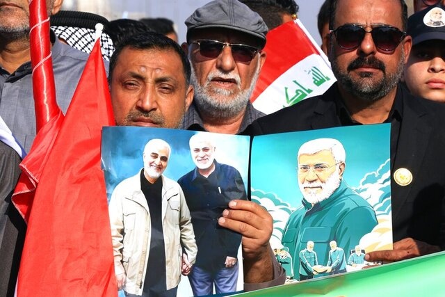 Supporters of the Popular Mobilization Forces hold a poster of Abu Mahdi al-Muhandis, deputy commander of the Popular Mobilization Forces and General Qassem Soleimani, head of Iran's Quds force during a rally to commemorate the anniversary of the killing of Soleimanil and al-Muhandis in a U.S. drone strike in Basra, Iraq, Friday, Jan. 8, 2021. (AP Photo/Nabil al-Jurani)