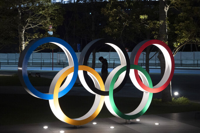 FILE - In this March 24, 2020, a man is seen through the Olympic rings in front of the New National Stadium in Tokyo. IOC officials say the Tokyo Olympics will open on July 23 and almost nothing now can stop the games from going forward. (AP Photo/Jae C. Hong, File)