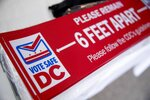 Social distancing stickers are visible at a voting center during primary voting in Washington, Tuesday, June 2, 2020. (AP Photo/Andrew Harnik)