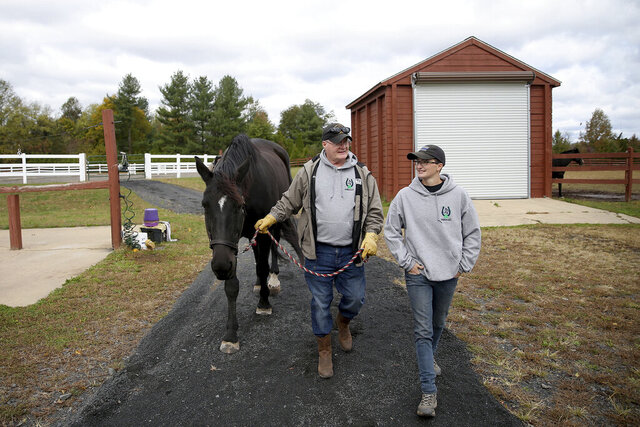This Oct. 17, 2019 photo, Dale Pitcher leads Ruby the horse back to the barn with instructor Alexis Daly, right, at Shamrock Reins in Pipersville, Pa.  Shamrock Reins offers equine therapy for veterans including Pitcher.  (Tim Tai/The Philadelphia Inquirer via AP)