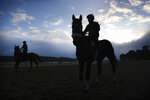 Horses and riders arrive to the track for workouts at Belmont Park in Elmont, N.Y., Friday, June 19, 2020. The Belmont Stakes is scheduled to run on Saturday. (AP Photo/Seth Wenig)
