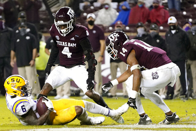 LSU wide receiver Terrace Marshall Jr. (6) catches a pass for a touchdown against Texas A&M defensive backs Erick Young (4) and Keldrick Carper (14) in an NCAA college football game Saturday, Nov. 28, 2020, in College Station, Texas. (AP Photo/Sam Craft)