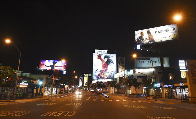 The Sunset Strip is bereft of cars and pedestrians at night as stay-at-home orders continue in California due to the coronavirus outbreak, Wednesday, April 1, 2020, in West Hollywood, Calif. (AP Photo/Chris Pizzello)