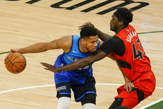 Milwaukee Bucks' Giannis Antetokounmpo tries to get past Toronto Raptors' Pascal Siakam during the first half of an NBA basketball game Thursday, Feb. 18, 2021, in Milwaukee. (AP Photo/Morry Gash)