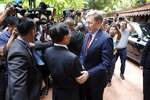 Cambodia National Rescue Party's President Kem Sokha, center left, shakes hands with U.S. Ambassador to Cambodia W. Patrick Murphy, center right, before a welcoming meeting at his house in Phnom Penh, Cambodia, Monday, Nov. 11, 2019. A Cambodian court has lifted some restrictions on detained opposition leader Kem Sokha, essentially ending his house arrest. (AP Photo/Heng Sinith)