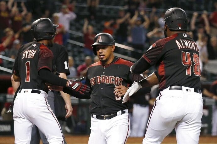 Arizona Diamondbacks' Eduardo Escobar, middle, celebrates with Jarrod Dyson (1) and Abraham Almonte (48) after all score runs against the Miami Marlins on a three-run double hit by Diamondbacks' Jake Lamb during the seventh inning of a baseball game, Monday, Sept. 16, 2019, in Phoenix. (AP Photo/Ross D. Franklin)