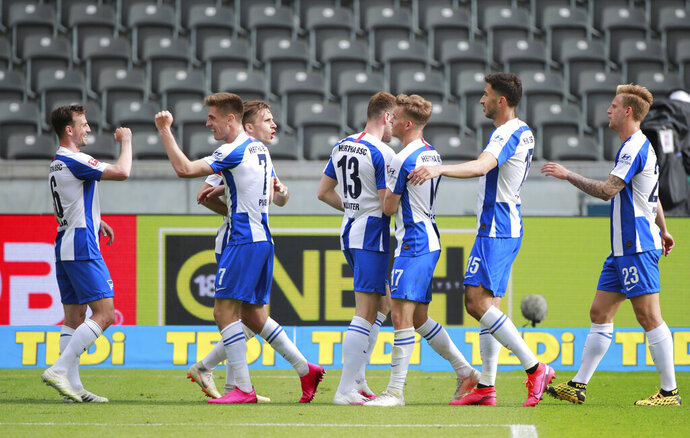 Hertha BSC's Krzysztof Piatek celebrates scoring their second goal with teammates during the German Bundesliga soccer match between Hertha Berlin and Augsburg at the Olympiastadion in Berlin, Germany, Saturday, May 30, 2020. Because of the coronavirus outbreak all soccer matches of the German Bundesliga take place without spectators. (Hannibal Hanschke/pool photo via AP)