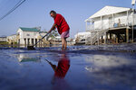 Cindy Rojas cleans mud and floodwater from her driveway in the aftermath of Hurricane Ida, Sunday, Sept. 5, 2021, in Lafitte, La. (AP Photo/John Locher)