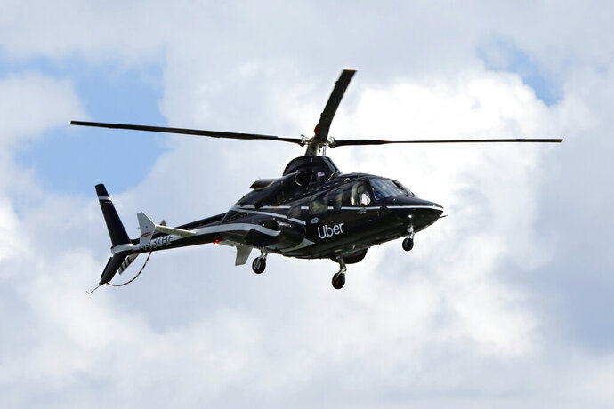 In this Wednesday, Oct. 2, 2019, photo an Uber helicopter approaches the Downtown Manhattan Heliport, in New York. The ride-hailing company expanded its helicopter service Thursday, Oct. 3, between lower Manhattan in New York City and John F. Kennedy International Airport, making it available to all Uber riders with iPhones instead of just those in the top tiers of its rewards program. Uber hopes to deploy it to Android users soon. (AP Photo/Richard Drew)