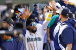 Seattle Mariners' J.P. Crawford is congratulated by teammates after scoring against the Houston Astros during the sixth inning of a baseball game Wednesday, Sept. 1, 2021, in Seattle. (AP Photo/Elaine Thompson)