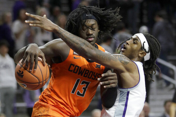 Oklahoma State guard Isaac Likekele (13) is covered by Kansas State guard Cartier Diarra, right, during the second half of an NCAA college basketball game in Manhattan, Kan., Tuesday, Feb. 11, 2020. Oklahoma State defeated Kansas State 64-59. (AP Photo/Orlin Wagner)