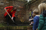 Britain's Liberal Democrats leader Jo Swinson finishes off planting an Acer tree in the garden of the Razumovsky music Academy watched by children of party supporters, as she campaigns in the Hampstead and Kilburn constituency in north London, Saturday, Nov. 16, 2019. Britain goes to the polls on Dec. 12. (AP Photo/Matt Dunham)