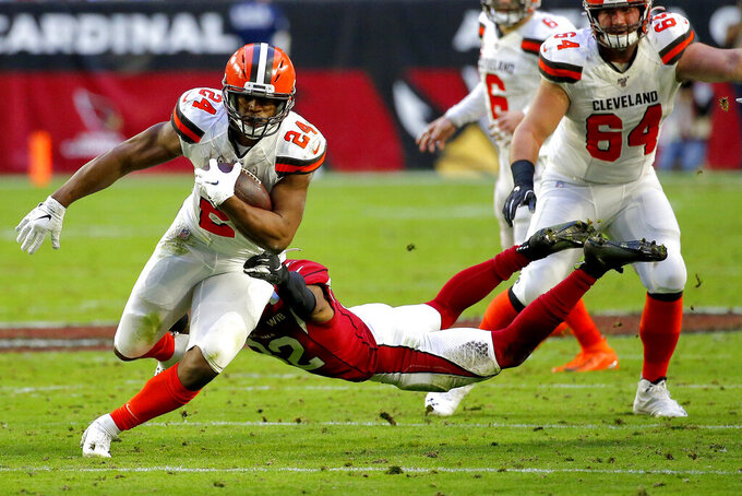 Cleveland Browns running back Nick Chubb (24) escapes the tackle of Arizona Cardinals strong safety Budda Baker during the second half of an NFL football game, Sunday, Dec. 15, 2019, in Glendale, Ariz. (AP Photo/Rick Scuteri)