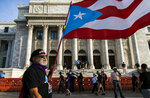 A demonstrator carries a Puerto Rican flag outside the Capitol where the Senate decided against the confirmation of Pedro Pierluisi as the new governor in San Juan, Puerto Rico, Monday, Aug. 5, 2019. Puerto Rico's Supreme Court on Monday agreed to rule on a lawsuit that the island's Senate filed in a bid to oust Pierluisi, a veteran politician recently sworn in as the island's governor. (AP Photo/Dennis M. Rivera Pichardo)