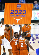 Texas guard Courtney Ramey (3) dances and holds an NCAA college basketball game championship poster for the Maui Invitational next to guard Matt Coleman III (2), Wednesday, Dec. 2, 2020, in Asheville, N.C. Texas beat North Carolina 69-67. Coleman was the MVP with the winning basket and high score of 22 points. (AP Photo/Kathy Kmonicek)