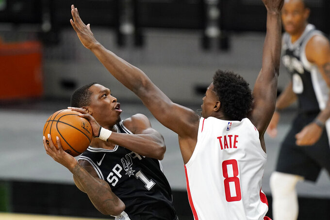 San Antonio Spurs guard Lonnie Walker IV (1) drives to the basket against Houston Rockets forward Jae'Sean Tate (8) during the first half of an NBA basketball game in San Antonio, Thursday, Jan. 14, 2021. (AP Photo/Eric Gay)