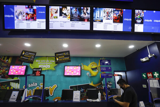 A moviegoer purchases tickets in the Cinepolis movie theater at Forum Buenavista mall, in Mexico City, Wednesday, Aug. 12, 2020. After being closed for nearly five months amidst the ongoing coronavirus pandemic, movie theaters in the capital reopened Wednesday at 30% capacity. (AP Photo/Rebecca Blackwell)