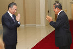 Chinese Foreign Minister Wang Yi, left, greets Cambodian Prime Minister Hun Sen prior to a meeting at Peace Palace in Phnom Penh, Cambodia, Monday, Oct. 12, 2020. The two countries signed a free trade agreement on Monday. (AP Photo/Heng Sinith)