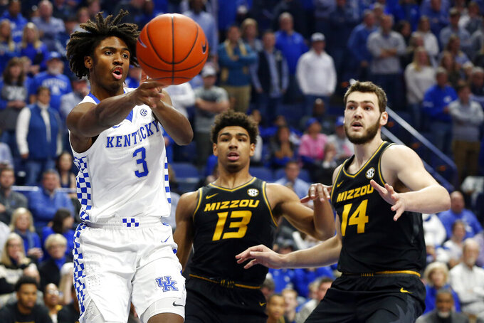Kentucky's Tyrese Maxey (3) passes around the defense of Missouri's Mark Smith (13) and Reed Nikko (14) during the first half of an NCAA college basketball game in Lexington, Ky., Saturday, Jan 4, 2020. (AP Photo/James Crisp)