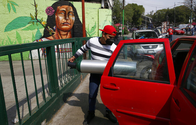 A person loads into the back seat of a car a tank filled with oxygen for a family member sick with COVID-19, in the Iztapalapa borough of Mexico City, Friday, Jan. 15, 2021. The city offers free oxygen refills for COVID-19 patients. (AP Photo/Marco Ugarte)
