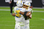Los Angeles Chargers tight end Hunter Henry, right, embraces quarterback Justin Herbert (10) after defeating the Las Vegas Raiders in overtime of an NFL football game, Thursday, Dec. 17, 2020, in Las Vegas. (AP Photo/David Becker)