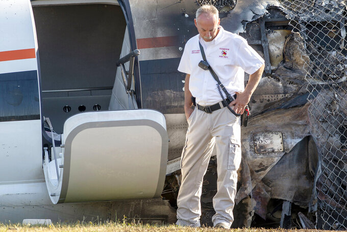 Elizabethton Deputy Fire Chief Steve Murray looks over the crash site, Friday, Aug. 16, 2019, of a plane that Dale Earnhardt Jr., his wife and daughter and two pilots and a dog were on when it crash landed Thursday at the Elizabethton Municipal Airport in Elizabethton, Tenn., Friday, Aug. 16, 2019. Earnhardt Jr. will take the weekend off from broadcasting to be with his wife and daughter after the crash near Bristol Motor Speedway. (David Crigger/Bristol Herald Courier via AP)