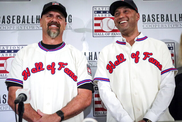 FILE - In this Jan. 22, 2020, file photo, former New York Yankees shortstop Derek Jeter, right, and former Colorado Rockies outfielder Larry Walker pose after receiving their Baseball Hall of Fame jerseys during a baseball news conference in New York.  Jeter and Walker and the rest of this year's Baseball Hall of Fame class will have to wait for their big moment at Cooperstown. The Hall of Fame announced Wednesday, April 29, 2020, that it has canceled its July 26 induction ceremony because of the coronavirus outbreak. (AP Photo/Bebeto Matthews, File)