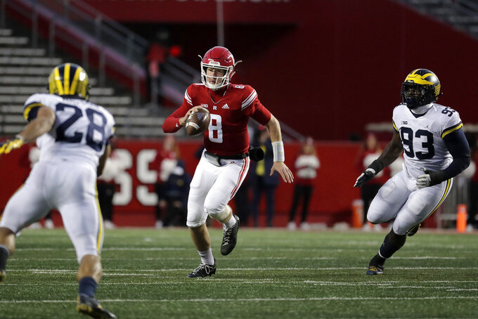 Rutgers quarterback Artur Sitkowski (8) scrambles as Michigan defensive back Brandon Watson (28) and defensive lineman Lawrence Marshall (93) try to stop him during the first half of an NCAA college football game, Saturday, Nov. 10, 2018, in Piscataway, N.J. (AP Photo/Julio Cortez)