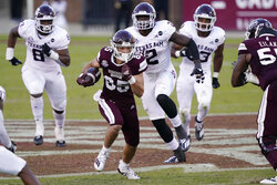 Texas A&M defenders run after Mississippi State wide receiver Austin Williams (85) as he heads upfield with a first down pass reception during the second half of an NCAA college football game in Starkville, Miss., Saturday, Oct. 17, 2020.  (AP Photo/Rogelio V. Solis)