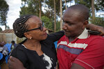 In this photo taken Thursday, March 14, 2019, sister Goreti Kimani consoles brother Chira Kageche at a prayers ceremony for their brother Catholic priest Rev. George Mukua Kageche, 40, who died in the plane crash in Ethiopia, held at his home in Githunguri, near Nairobi, in Kenya. The Rev. George Kageche Mukua was one of 32 Kenyans killed when Ethiopian Airlines flight 302 faltered shortly after takeoff from Addis Ababa and crashed, a numbingly high toll on a flight carrying people from 35 countries. (AP Photo/Sayyid Abdul Azim)