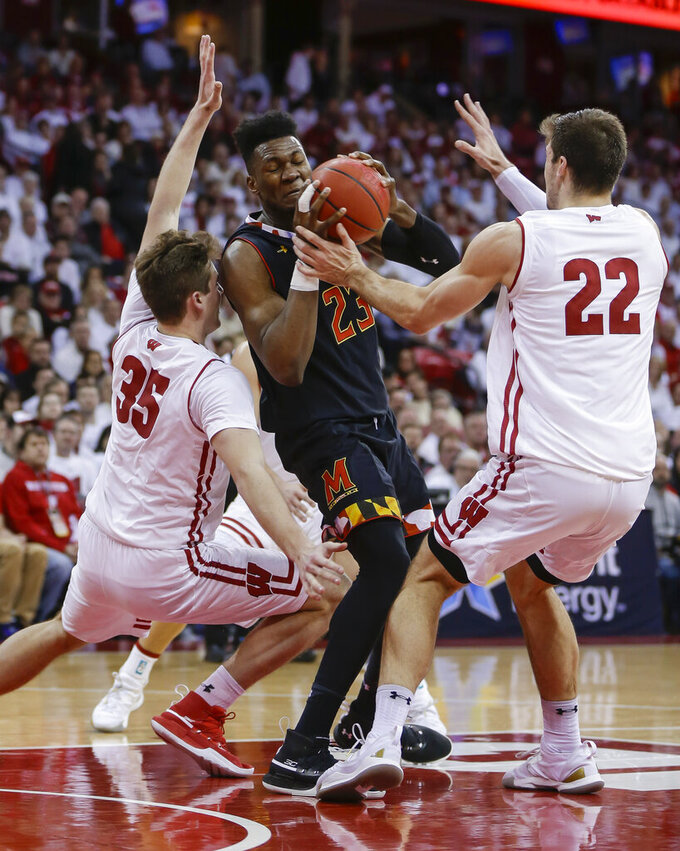 Maryland's Bruno Fernando (23) drives between Wisconsin's Nate Reuvers (35) and Ethan Happ (22) during the first half of an NCAA college basketball game Friday, Feb. 1, 2019, in Madison, Wis. (AP Photo/Andy Manis)