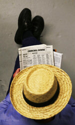 FILE - In this May 3, 2014, file photo, a man looks over a racing form before the 140th running of the Kentucky Derby horse race at Churchill Downs, in Louisville, Ky. Picking a horse to win the Kentucky Derby is easy. Start with a daily racing program that lists entrants for each race and information including odds, jockey, trainer, silks, saddle towel color and past performances. (AP Photo/Charlie Riedel, File)