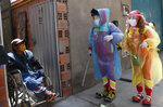 Clowns Perlita and Tapetito, wearing protective gear amid the new coronavirus pandemic, speak with resident Enrique Zeballos as they arrive to disinfect his home free of charge, in El Alto, Bolivia, Friday, Sept. 11, 2020. The lack of traditional employment for the clowns due to the pandemic has led them towards other avenues of making money. But for people with limited income they provide their disinfection services free of charge. (AP Photo/Juan Karita)