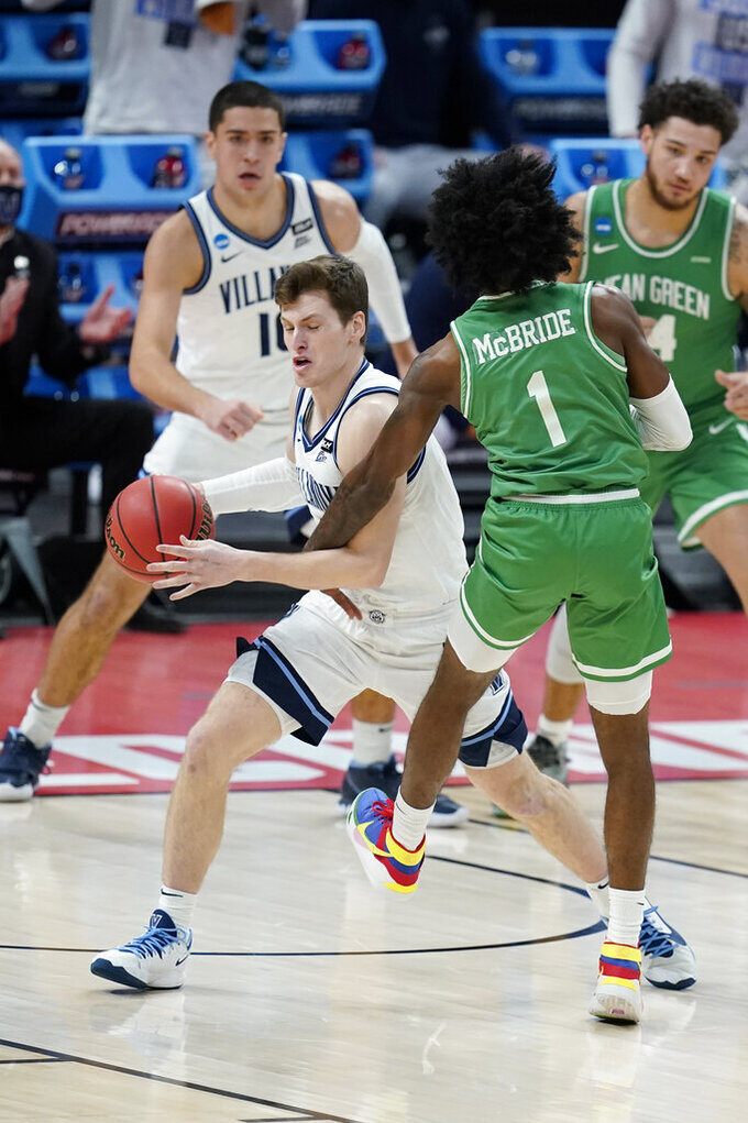 Villanova's Chris Arcidiacono (4) is fouled by North Texas's Mardrez McBride (1) during the first half of a second-round game in the NCAA men's college basketball tournament at Bankers Life Fieldhouse, Sunday, March 21, 2021, in Indianapolis. (AP Photo/Darron Cummings)