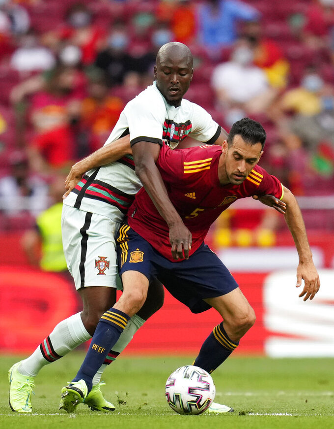 Portugal's Danilo Pereira, left, challenges for the ball with Spain's Sergio Busquets during the international friendly soccer match between Spain and Portugal at the Wanda Metropolitano stadium in Madrid, Spain on Friday June 4, 2021. (AP Photo/Manu Fernandez)