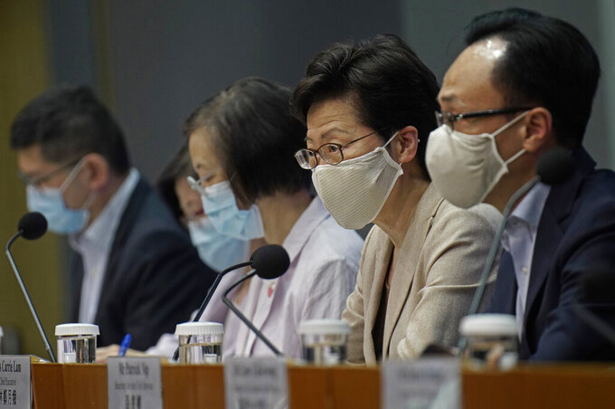 """Hong Kong Chief Executive Carrie Lam, second from right, listens to reporters questions during a press conference held in Hong Kong, Sunday, July 19, 2020. Lam introduced renewed anti-virus measures Sunday, saying the southern Chinese city's situation is """"really critical"""" and adding that she sees """"no sign"""" that it's under control. The new restrictions make mask wearing mandatory in any public place including inside buildings, and put non-essential civil servants back to work at home. (AP Photo/Vincent Yu)"""
