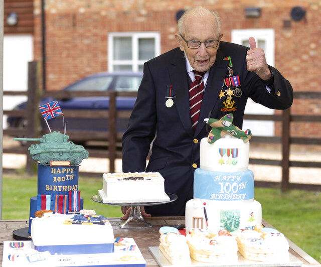 In this photo provided by Capture the Light Photography,  Second World War veteran Captain Tom Moore poses with birthday cakes as he celebrates his 100th birthday, in Bedford, England, Thursday April 30, 2020. A British army veteran who started walking laps in his garden as part of a humble fundraiser for the National Health Service is celebrating his 100th birthday after warming the hearts of a nation that donated millions of pounds to back his appeal. (Emma Sohl/Capture the Light Photography via AP)