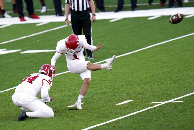 Rutgers kicker Valentino Ambrosio, right, with Zach Feagles holding, kicks a field goal against Maryland during overtime of an NCAA college football game, Saturday, Dec. 12, 2020, in College Park, Md. Rutgers won 27-24 in overtime. (AP Photo/Julio Cortez)