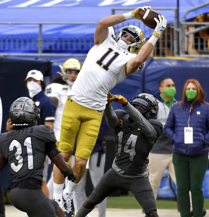 Notre Dame wide receiver Ben Skowronek pulls in a pass for a touchdown against Pitt defensive backs Erick Hallett and Marquis Williams in the second quarter of an NCAA college football game, Saturday, Oct. 24, 2020, in Pittsburgh. (Matt Freed/Pittsburgh Post-Gazette via AP)
